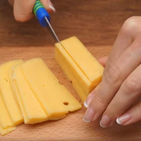 100 г сыра нарезаем тонкими пластинками.