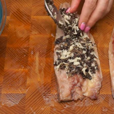 На подготовленное филе выкладываем начинку.  На самый край со стороны головы начинку не кладем, чтобы она не выпадала при сворачивании.