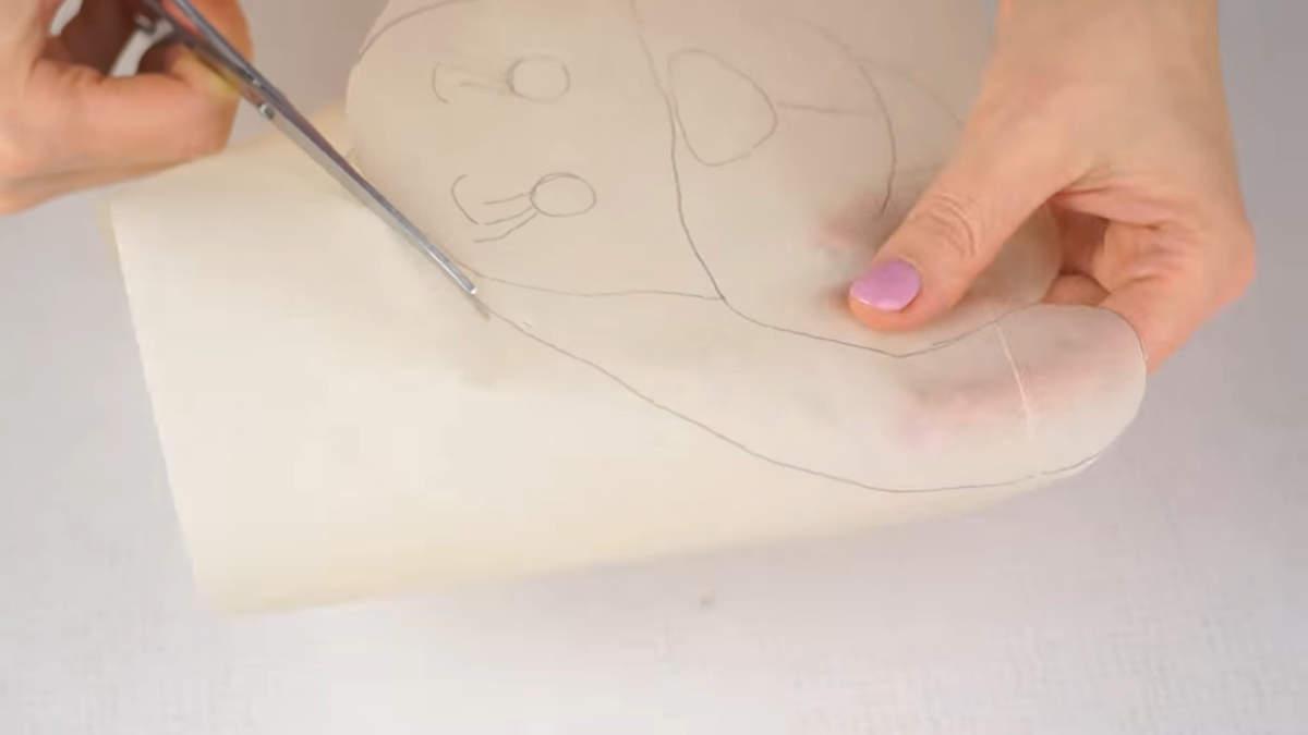 На пергаментной бумаге рисуем мордочку собачки и вырезаем ее по контуру. Ссылку на мордочку собачки я оставлю в описании под видео.