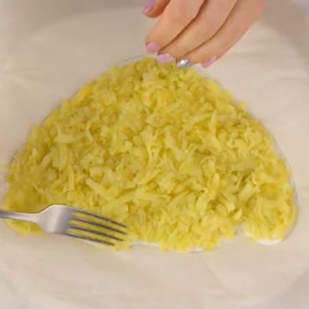 Трафарет из пергамента кладем на тарелку, в которой будем собирать салат. Первым слоем кладем тертый картофель и равномерно распределяем его по тарелке внутри трафарета.