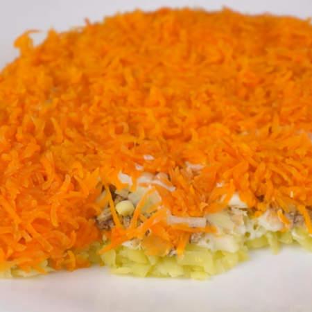 Следующим слоем выкладываем тертую морковь. Этот слой, там где должны находиться ушки, нужно покрыть морковкой не только сверху, но и по бокам.