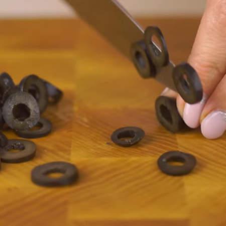 Маслины нарезаем тонкими колечками.