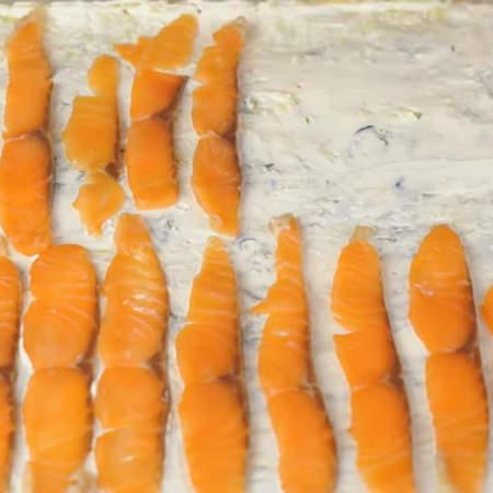 Сверху на сыр выкладываем кусочки нарезанной рыбы.