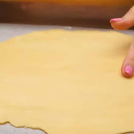 От готового теста отделяем небольшой кусок и тонко раскатываем его на пергаментной бумаге присыпанной мукой.