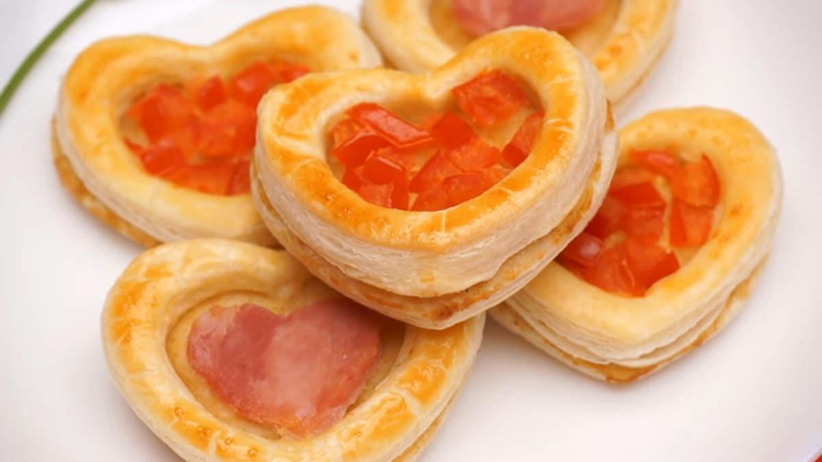 Закуска Сердечки из слоеного теста получилась нежной, вкусной и романтичной. Готовится она совсем не сложно.  Обязательно порадуйте свою вторую половинку таким романтичным блюдом.