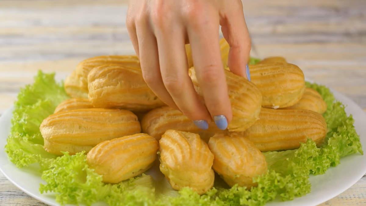 Выкладываем закусочные эклеры на блюдо, украшенное листьями салата.  Изысканная закуска на праздничный стол готова!
