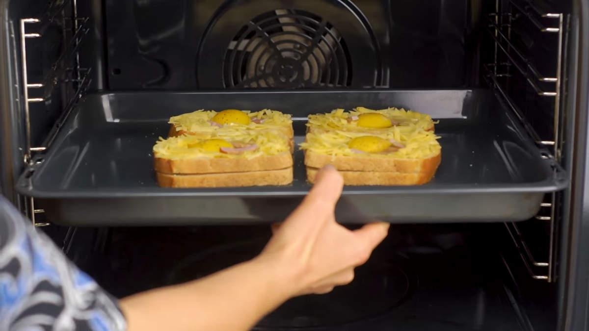 Бутерброды ставим в духовку, разогретую до 180 градусов. Запекаем примерно 15 минут. Белок должен загустеть, а желток остаться еще жидким.