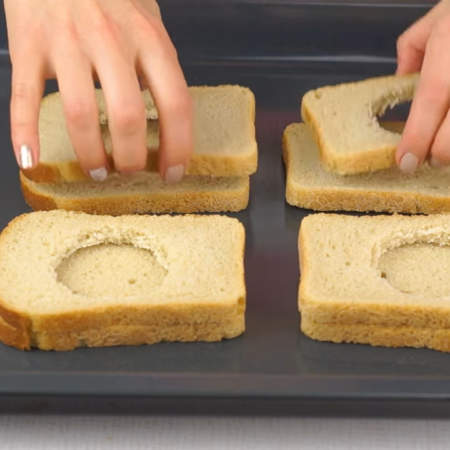 На противень выкладываем целый ломтик хлеба, а на него ломтик с вырезанным кружком.