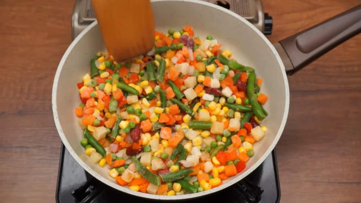 Сначала подготовим овощи. 400 г замороженной овощной смеси насыпаем в сковороду и накрываем крышкой. тушим на небольшом огне примерно 15 минут. Чтоб овощи стали мягкие. Готовую овощную смесь снимаем с плиты и даем ей остыть.