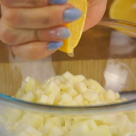 Порезанное яблоко кладем в миску и выдавливаем на него примерно столовую ложку лимонного сока. Это делается для того, чтобы яблоко не темнело. Яблоко с лимонным соком перемешиваем.