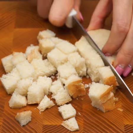 Сначала подготовим все ингредиенты: 2 кусочка белого хлеба нарезаем кубиками.