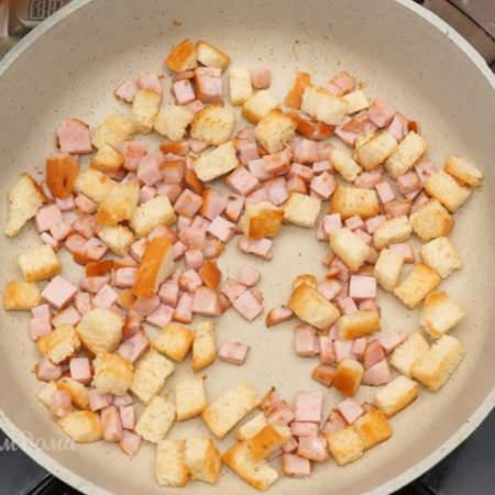 Сюда же, к сухарикам,  добавляем уже нарезанную колбасу, все немного обжариваем для вкуса и аромата.