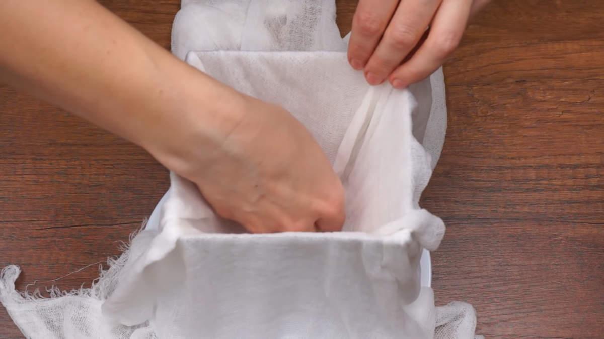 Ставим форму на тарелку вверх дном. Застилаем ее марлей сложенной в два раза. Для того чтоб марлю красивее выложить в форме, ее нужно обязательно смочить водой и выкрутить. Марлю красиво распределяем по форме. Загибы стараемся укладывать по углам.