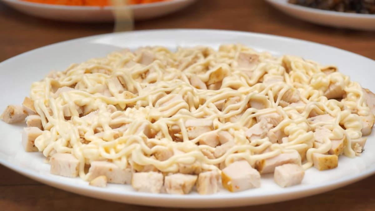 Собираем салат. Первым слоем равномерно выкладываем нарезанное куриное филе. Наносим майонез.