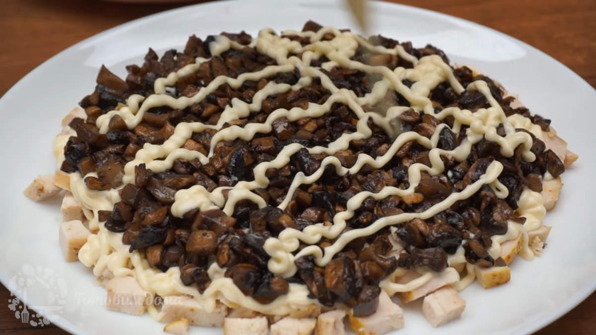 Вторым слоем кладем уже остывшие подготовленные грибы. Опять наносим сеточку из майонеза.