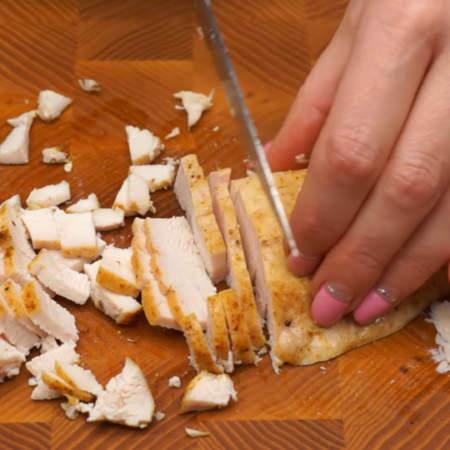 300 г  запеченного куриного филе нарезаем небольшими кубиками.