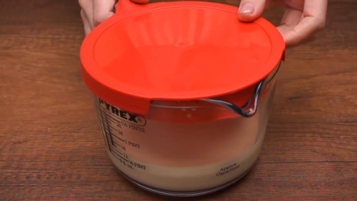 Тесто переливаем в емкость с носиком, у меня это мерная кружка. Накрываем крышкой и даём ему настояться минимум 2 часа. Я тесто оставляю в холодильнике на ночь.