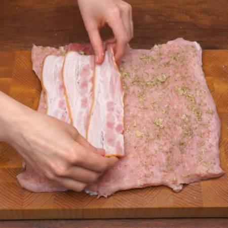 С одной стороны на мясо кладем 3 полоски нарезанного бекона.