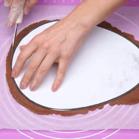 На тесто кладем трафарет в форме яйца, вырезанный из бумаги. С помощью ножа вырезаем из раскатанного теста яйца. Так вырезаем все три кожа.