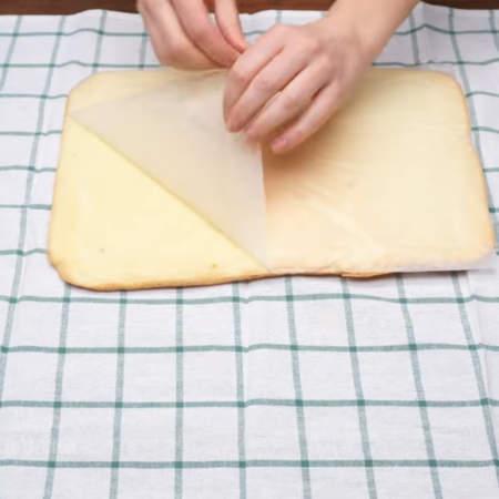 Испеченный бисквит сразу же горячим кладем на полотенце и снимаем пергаментную бумагу.