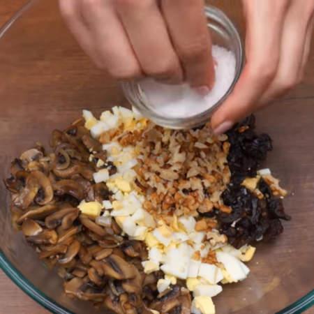 В миску кладем жареные грибы, нарезанные яйца, чернослив и грецкие орехи.  Начинку немного солим.