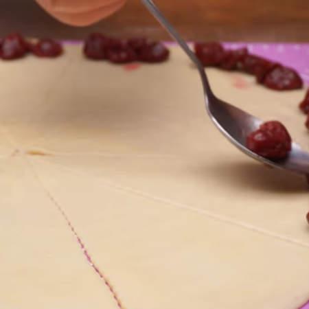 На каждый треугольник теста, с краю, кладем консервированные вишни.