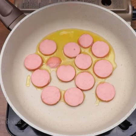На сковороду наливаем немного растительного масла и кладем нарезанные сардельки.