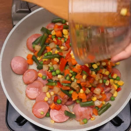примерно 2-3 минуты с двух сторон до румяной корочки. В сковороду к обжаренным сарделькам насыпаем 400 г смеси замороженных овощей. Я использую Мексиканскую смесь. Овощи могут быть как замороженными, так и уже размороженными при комнатной температуре или в холодильнике. Все перемешиваем.