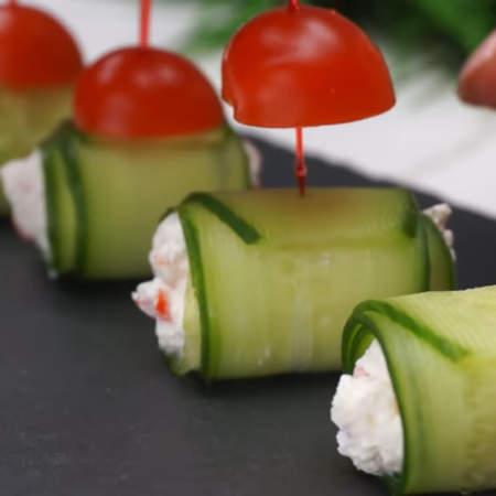 Каждую половинку помидора протыкаем шпажкой, а затем шпажкой с помидором прокалываем рулетик из огурца. Вместо шпажек можно использовать деревянные зубочистки.