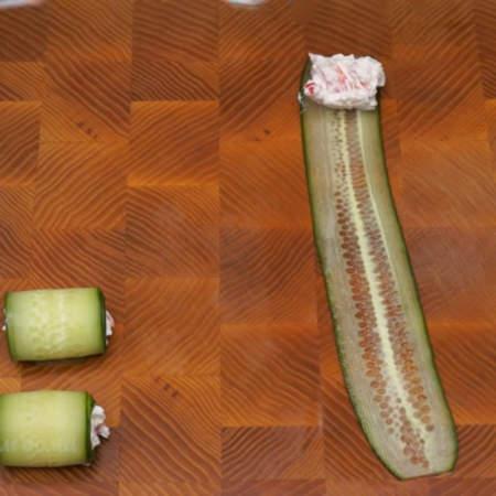 На доску кладем пластинку огурца. С одной стороны на огурец кладем примерно 1 ч. л. подготовленной начинки.