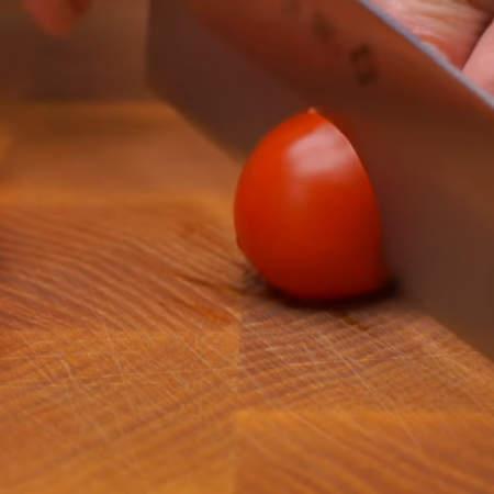 Готовые рулетики выкладываем на блюдо. Маленькие помидоры черри разрезаем пополам.