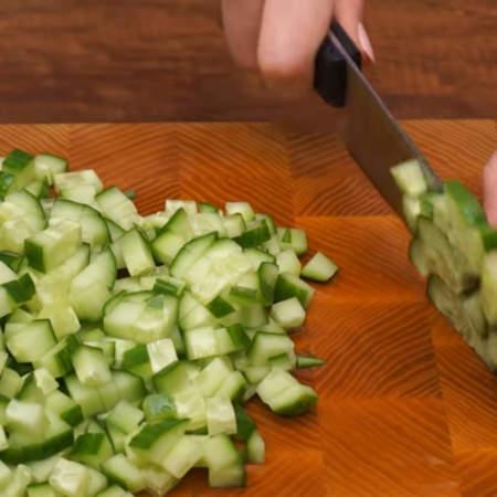 Сначала подготовим ингредиенты. 2 длинных огурца общим весом примерно 400 г нарезаем сначала на пластинки, а затем кубиками.