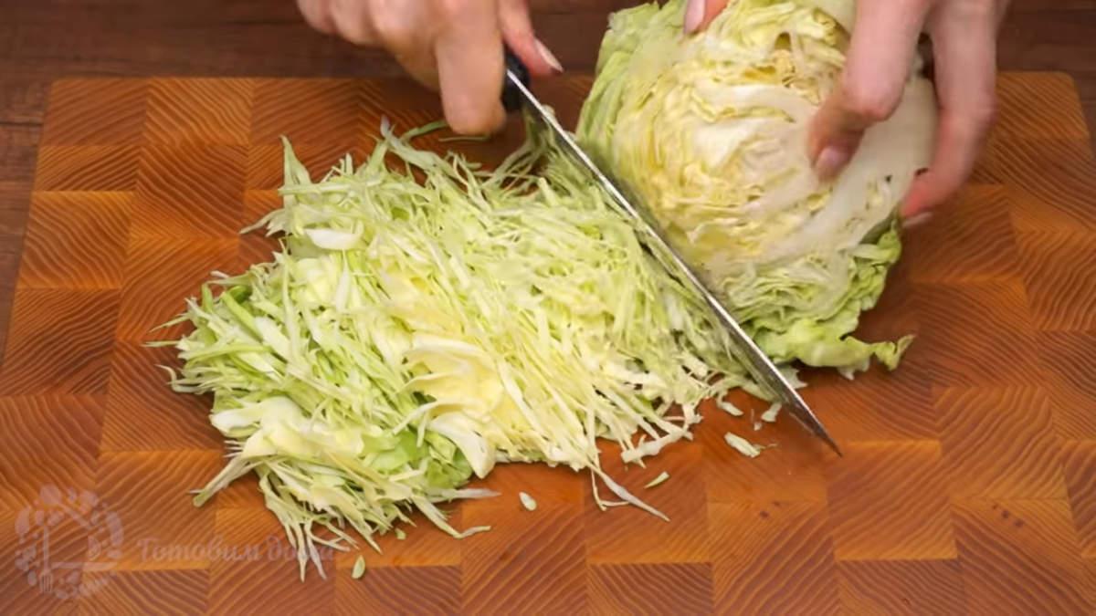 0,5 кг молодой капусты мелко шинкуем ножом. В оригинальном рецепте салата используется пекинская капуста. Но так как сейчас весна пекинской капусты нет, я ее заменила молодой белокочанной капустой.
