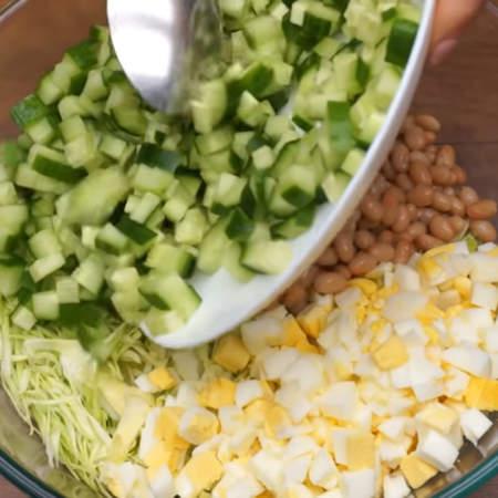 В миску кладем нашинкованную капусту, нарезанные яйца, 1 банку консервированной фасоли, и нарезанный огурец.