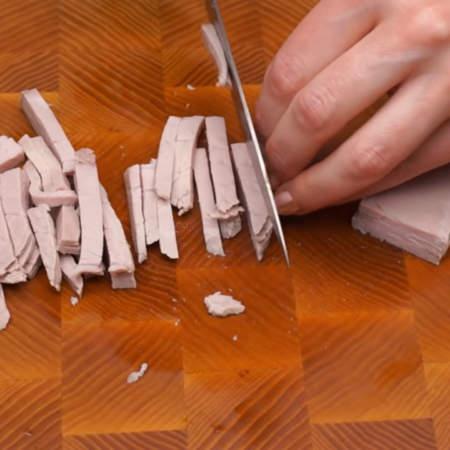 200 г отварного мяса нарезаем брусочками поперек волокон. Я отварила свинину, но также можно использовать говядину.