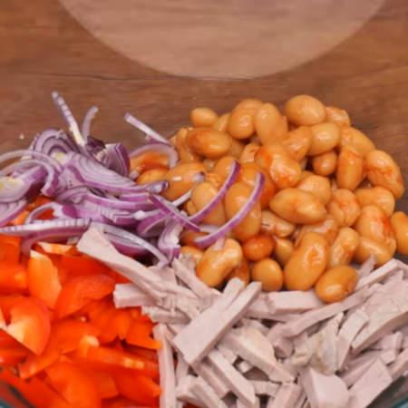 В большую миску кладем нарезанный перец, подготовленное мясо, одну пол литровую банку консервированной фасоли, нарезанный лук и петрушку.