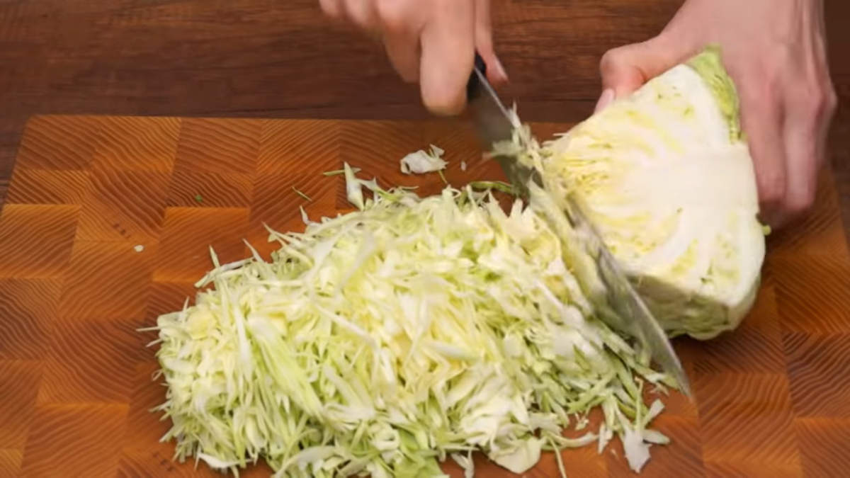 Сначала подготовим все ингредиенты для салата. Мелко шинкуем пол кочана молодой капусты.