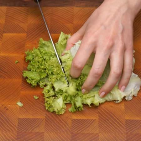 Примерно 150 г листового салата нарезаем большими кусками. 5 листов салата оставляем для украшения тарелки на которой будем подавать салат на стол. Всего понадобится 200 г салата.