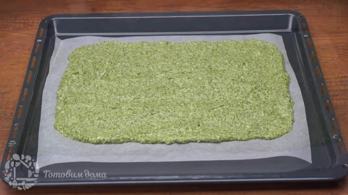 Приготовленное бисквитное тесто выкладываем на противень застеленный пергаментной бумагой. Шпинатную массу разравниваем тонким слоем формируя прямоугольник размером 20 на 30 см. Пергаментную бумагу нужно брать качественную и гладкую, к шершавой бумаге бисквит прилипнет .