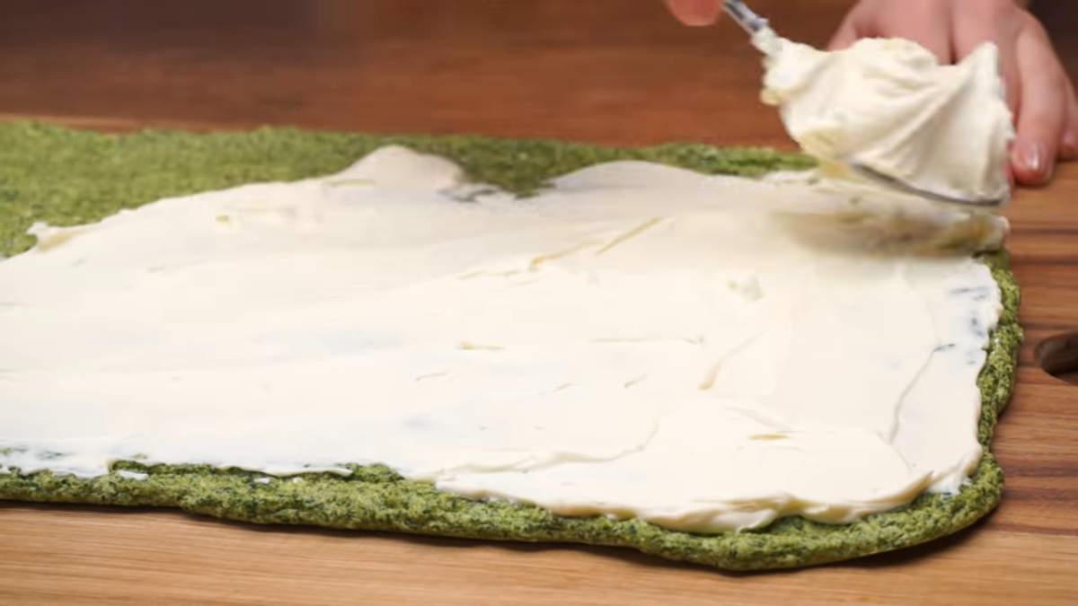 Переворачиваем бисквит гладкой стороной вниз. Равномерно намазываем сырную массу по всей поверхности на шпинатный бисквит.