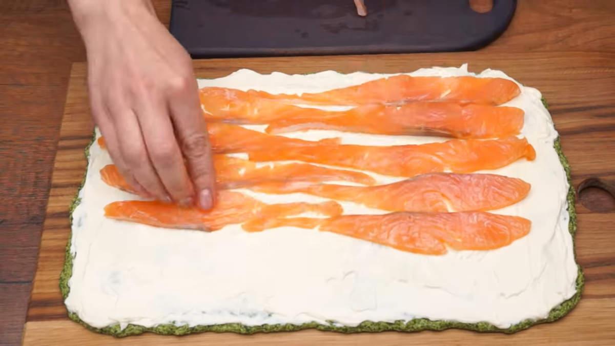На сливочный сыр выкладываем кусочки рыбы. На самый край рыбу класть не нужно, так рулет не будет лучше держать свою форму.