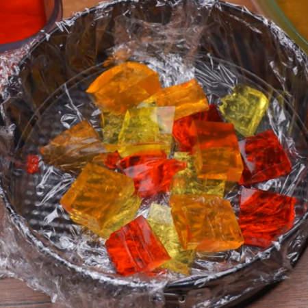 В подготовленную форму выкладываем желейные кубики. Сначала кладем 4-5 кубиков одного цвета, а затем второго и третьего. Так чередуя выкладываем все цвета.