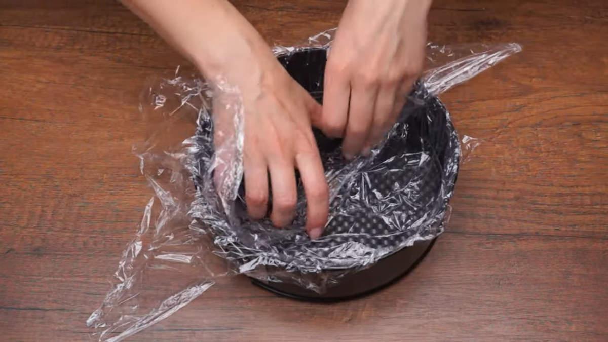 Подготовим форму для торта. Я взяла разъемную форму диаметром 21 см. Чтобы жидкость не вытекла через стыки формы, застилаем ее пищевой пленкой.