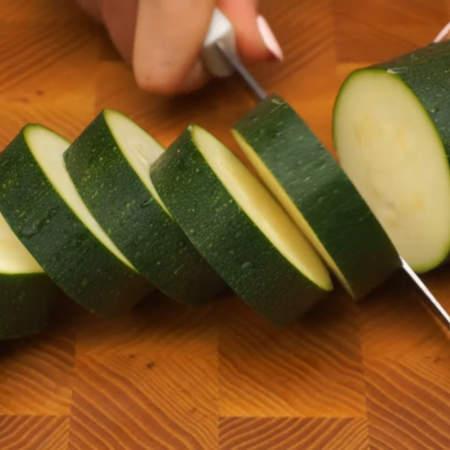Примерно 1 кг цукини моем и нарезаем кружочками толщиной 1.5 - 2 см. Вместо цукини можно взять кабачки.