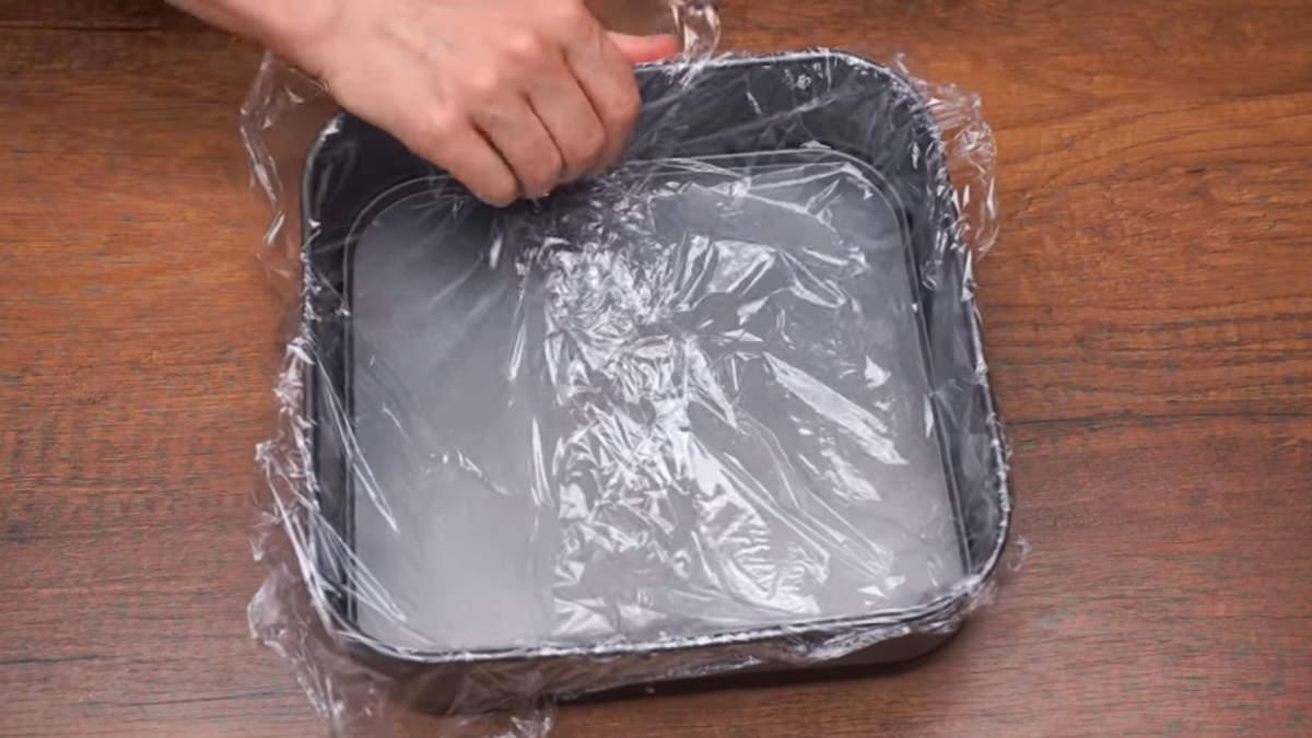 Готовим форму для торта. Я взяла квадратную форму размером 23 на 23 см. В середине форму аккуратно застилаем пищевой пленкой для того, чтобы металлическая форма не окислялась и торт легко вынимался из формы.