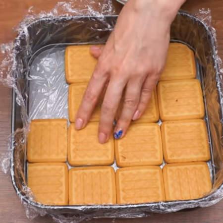 Первым слоем кладем песочное печенье. Печенье нужно складывать плотно друг к другу, а лишние части печенья, которые не помещаются в форму, обрезаем ножом до нужного размера.