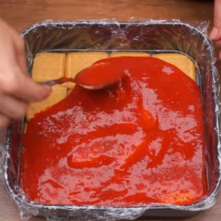 На слой из печенья выливаем немного клубничного пюре. Слой из клубничного пюре по толщине должен быть немного тоньше, чем толщина печенья.