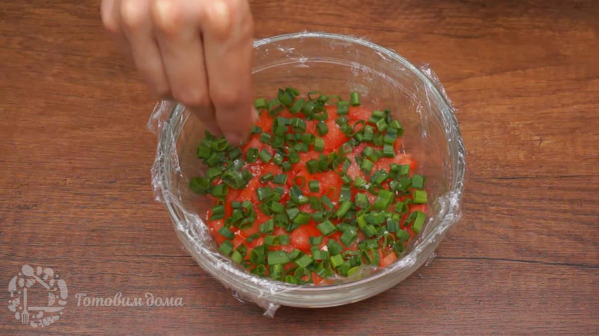Вторым слоем кладем половину нарезанных помидоров. Сверху посыпаем зеленым луком. Немного солим. Наносим сеточку из майонеза.