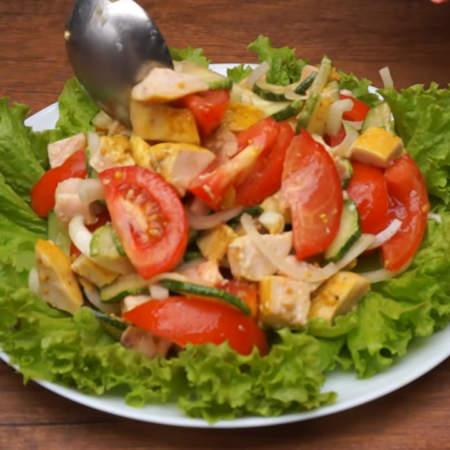 Сверху на листья салата выкладываем приготовленный салат.
