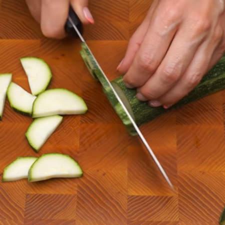 Один небольшой цуккини разрезаем вдоль и нарезаем полукружочками. Сильно тонко нарезать не нужно.